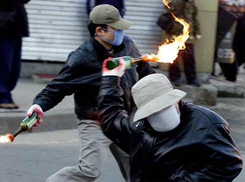 SOUTH KOREAN PROTESTERS THROW FIRE BOMBS AT RIOT POLICE IN PUPYONG.